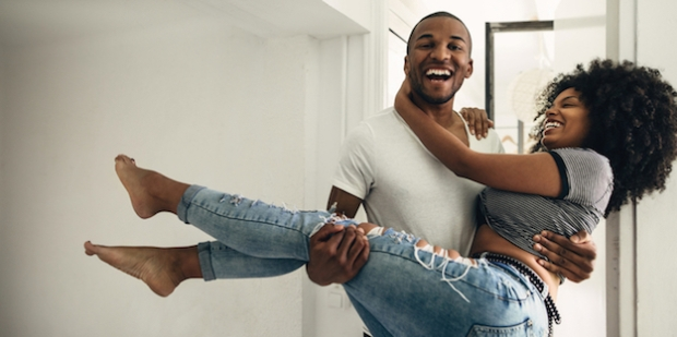 black-couple-laughing-carrying-woman